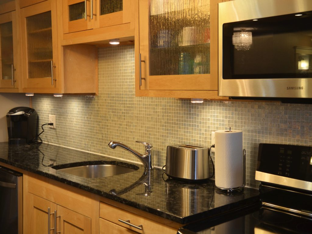 Modern birch kitchen with granite counters, glass backsplash, and stainless steel appliances